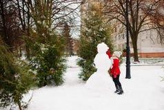 La muchacha de la edad de escuela construye un muñeco de nieve Imagen de archivo