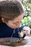 La muchacha de la escuela toma una bebida Fotos de archivo