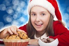 La muchacha de la feliz Navidad quiere comer la galleta Fotografía de archivo