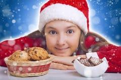 La muchacha de la feliz Navidad quiere comer la galleta Imagen de archivo libre de regalías