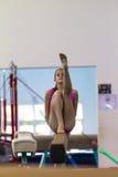 La muchacha de la gimnasia mueve el haz Fotos de archivo