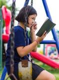 La muchacha de la lectura balancea cadenas Imagenes de archivo