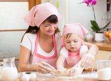 La muchacha de la madre y del niño cuece las galletas en la cocina Foto de archivo libre de regalías