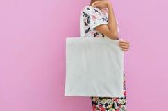 La muchacha de la maqueta está sosteniendo el bolso en blanco del algodón Compras hechas a mano del eco Imagenes de archivo