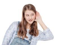La muchacha de la moda de los jóvenes lleva a cabo su mano cerca de su oído e ISO que escucha Fotografía de archivo libre de regalías
