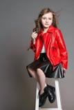 La muchacha de la moda en actitudes rojas de una chaqueta y hace muecas y hace una cara Estudio de la foto en un fondo gris Cumpl Fotos de archivo