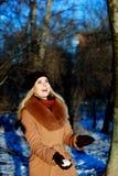 La muchacha de la nieve que se divierte el invierno, alista para lanzar la bola de nieve Imagen de archivo libre de regalías