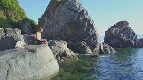La muchacha de la opinión del abejón lee el libro contra el acantilado en el mar en la salida del sol