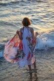 La muchacha de la parte posterior se coloca en el agua en la playa, controles se viste de largo hacia arriba con las manos Imagenes de archivo
