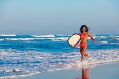 La muchacha de la persona que practica surf en bikini con la tabla hawaiana corre a lo largo de la playa del océano Imagenes de archivo