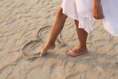 La muchacha de la pierna dibuja en el corazón de la arena Fotos de archivo