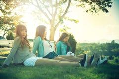 La muchacha de la sonrisa de tres Asia se sienta en hierba verde Imagenes de archivo