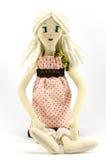 la muchacha de la Trapo-muñeca con el pelo rubio se vistió en vestido rosado manchado en el fondo blanco Fotos de archivo libres de regalías