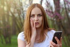 La muchacha de las mujeres jovenes consigue malas noticias en el teléfono celular de Smartphone Teléfono móvil del control de Wom Foto de archivo libre de regalías
