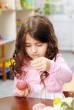 La muchacha de Liile pinta un huevo de Pascua Foto de archivo libre de regalías