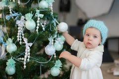 La muchacha de Littlt que adorna un árbol de navidad juega, día de fiesta, regalo, decoración, Año Nuevo, la Navidad, forma de vi Fotos de archivo libres de regalías