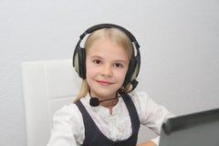 La muchacha de Llittle se sienta delante de un ordenador portátil con los auriculares y aprende Foto de archivo libre de regalías