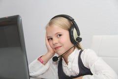 La muchacha de Llittle se sienta delante de un ordenador portátil con los auriculares y aprende Foto de archivo