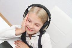 La muchacha de Llittle se sienta delante de un ordenador portátil con los auriculares y aprende Imagen de archivo libre de regalías