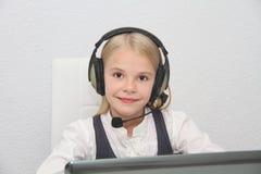 La muchacha de Llittle se sienta delante de un ordenador portátil con los auriculares y aprende Imagen de archivo