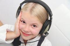 La muchacha de Llittle se sienta delante de un ordenador portátil con los auriculares y aprende Fotografía de archivo libre de regalías