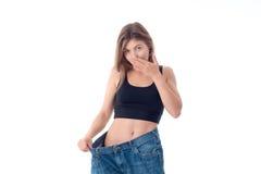 La muchacha de los deportes llevó los pantalones grandes y las maravillas se aíslan en un fondo blanco Fotografía de archivo