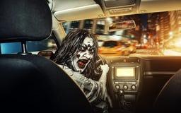 La muchacha de los Undead con la cara sangrienta monta en el coche imagen de archivo