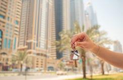 La muchacha de la mano lleva a cabo las llaves El concepto de comprar un apartamento o un coche en Dubai Primer de la mano fotos de archivo