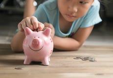 La muchacha de la mano puso la moneda a la hucha, ahorrando el dinero foto de archivo