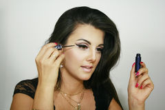 La muchacha de maquillaje hermosa pone su trazador de líneas del ojo, línea agradable fotos de archivo libres de regalías
