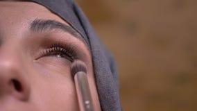 La muchacha de maquillaje que pone los sombreadores de ojos usando el cepillo para la mujer musulmán en hijab que mira hacia arri metrajes
