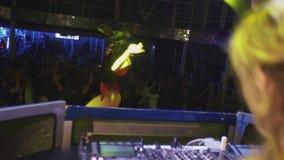 La muchacha de Mc y la muchacha de DJ en máscaras de las liebres bailan en etapa en club nocturno mixing booty almacen de metraje de vídeo