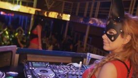 La muchacha de Mc y la muchacha de DJ en máscaras de las liebres bailan en etapa en club nocturno Placa giratoria booty almacen de video