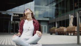 La muchacha de moda atractiva en vidrios elegantes y pelo largo se sienta en pasos cerca del edificio de oficinas metrajes