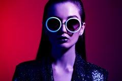 La muchacha de la moda con el pelo largo y las gafas de sol redondas en un vestido brillante negro presenta en la luz de neón en  fotografía de archivo