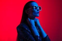 La muchacha de la moda con el pelo largo y las gafas de sol redondas en un vestido brillante negro presenta en la luz de ne?n en  foto de archivo libre de regalías