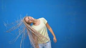 La muchacha de moda del inconformista que la sacudía trenzó las coletas del pelo y el giro alrededor en fondo azul almacen de metraje de vídeo