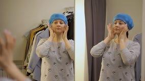 La muchacha de moda en la tienda intenta encendido la boina cerca del espejo metrajes