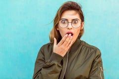 La muchacha de la moda en vidrios redondos coloca la presentación cerca de una turquesa wal fotos de archivo