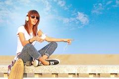 La muchacha de moda escucha la música con smartphone Fotos de archivo libres de regalías