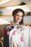 la muchacha de moda hermosa en el sombrero que elige la ropa con venta marca con etiqueta foto de archivo
