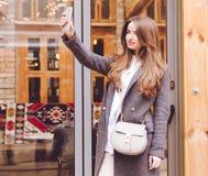 La muchacha de moda hermosa en pantalones y zapatillas de deporte grises de la capa con un bolso de moda hace smartphone del self Fotos de archivo libres de regalías