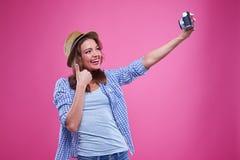 La muchacha de moda sonriente está tomando el selfie contra fondo rosado Imagen de archivo