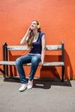 La muchacha de moda sonriente que disfruta del cierre observa en escuchar la música Fotografía de archivo libre de regalías