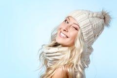La muchacha de la Navidad, sonrisa hermosa joven y da un guiño sobre azul Foto de archivo libre de regalías