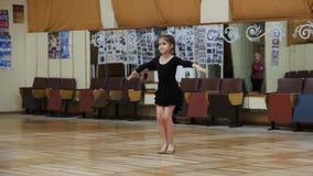 La muchacha de nueve años entra para los deportes que bailan en el pasillo de danza viejo metrajes