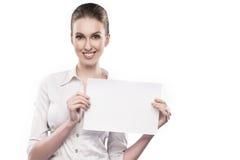 La muchacha de oficina en la blusa blanca sostiene los papeles en manos y sonrisas aislados en blanco Imágenes de archivo libres de regalías