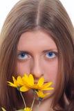 La muchacha de ojos azules con una flor salvaje amarilla Imagen de archivo