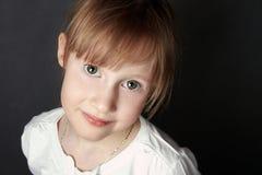 La muchacha de ojos verdes con las pecas mira emprendedor en la cámara Fotografía de archivo libre de regalías