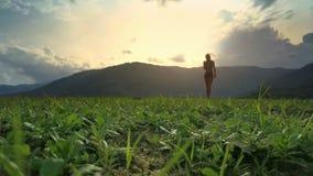 La muchacha de la opinión de Flycam camina en hierba contra silueta de la colina